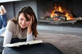 Porträtt av vacker kvinna läser bok vid eldstaden — Stockfoto