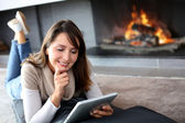 Woman using digital tablet laying by fireplace — Photo
