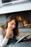 Woman using digital tablet laying by fireplace — Stock Photo