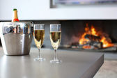 Closeup of champaign glasses set by fireplace — Stock Photo