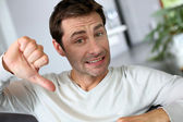 Discontented man showing thumb down — Stock Photo