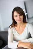 Aantrekkelijke vrouw zitten in de bank thuis — Stockfoto