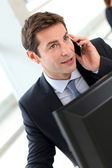 Businessman in office talking on the phone — Stock Photo