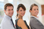 Cheerful business team standing in hallway — Stock Photo
