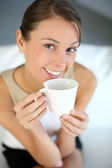 Attractive woman relaxing in sofa with cup of tea — Stock Photo
