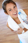 Cheerful fitness girl drinking water after exercising — Stock Photo