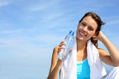 Thirsty fitness girl holding bottle of water — Stock Photo