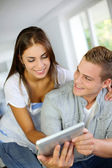 Young couple websurfing on electronic tablet — Stock Photo