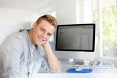 Portrait of young man sitting in front of computer — Stock Photo