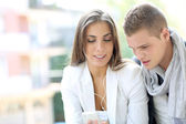 Young couple using smartphone in the street — Stock Photo