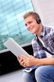 College student using digital tablet and headphones — Stock Photo