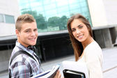 Young couple standing outside university campus — Stock Photo