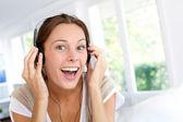 Kulaklık ile müzik dinlerken neşeli genç kadın — Stok fotoğraf