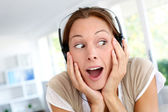 Cheerful young woman listening to music with headphones — Stock Photo