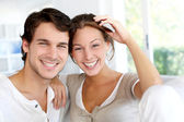 Portrait of smiling young couple at home — Stockfoto
