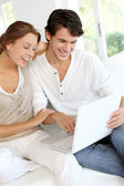 Happy young couple using laptop computer at home — Stock Photo