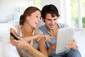 Vrolijke paar kiezen van tv-programma op digitale tablet pc — Stockfoto