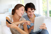 Cheerful couple choosing tv program on digital tablet — Stock Photo