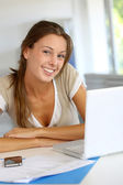 Portrait of smiling woman working on laptop at home — Stock Photo