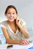 Smiling young woman working from home on laptop — Stock Photo