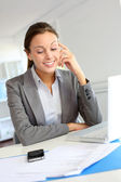 Smiling businesswoman sitting at her desk — Stock Photo