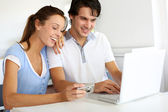 Couple at home uploading photographies on internet — Stok fotoğraf