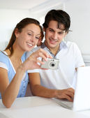 Couple at home uploading photographies on internet — Stock Photo