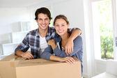 笑みを浮かべてカップル新しい家でボックスに傾いています。 — ストック写真