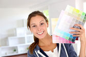 Smiling girl holding colour charts to decorate house — Stock Photo