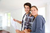 Nuevos propietarios en casa mirando plano — Foto de Stock
