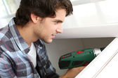 Repairman fixing door with electric drill — Stock Photo