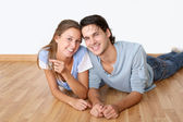 Cheerful couple laying down wooden floor — Stock Photo