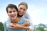 Man giving piggyback ride to girlfriend outside — Stock Photo
