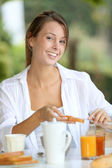 Young woman having bread for breakfast — Stock Photo