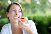Smiling woman eating peach for breakfast — Stock Photo