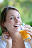 Closeup of woman drinking orange juice from glass — Stock Photo