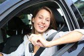 Cheerful girl holding car keys from window — Stock fotografie