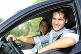 Cheerful couple driving car — Stok fotoğraf