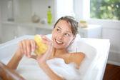Beautiful woman using bath sponge — Stock Photo