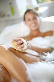 Woman in bathtub scrubbing her legs — Stock Photo