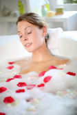 Beautiful woman relaxing in bath with rose petals — Stock Photo