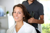 Woman having her hair dried by hairdresser — Stock Photo