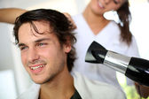 Young man in beauty salon having his hair dried — Stok fotoğraf