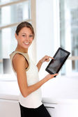 Businesswoman standing in office with digital tablet — Stock Photo