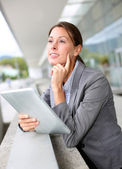 Executive woman standing outside with digital tablet — Stock Photo