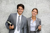 Cheerful business standing on grey background — Stock Photo