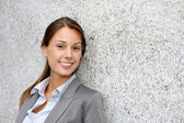 Smiling executive woman leaning on grey wall — Stock Photo