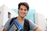 Cheerful student standing outside college building — Stock Photo