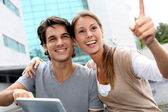 Students using tablet outside and pointing at something — Stock Photo