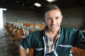 Portrait of smiling breeder in barn — Stock Photo